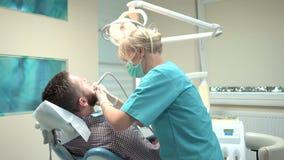 Dent femelle de perçage de dentiste de patient dans la clinique dentaire Tir de glisseur, laissé banque de vidéos