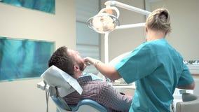 Dent femelle de perçage de dentiste, regardant à l'appareil-photo Tir de glisseur, droite banque de vidéos