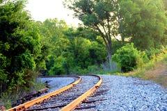 Dent vide de voie ferrée courbant dans un fond de beaux arbres photo stock