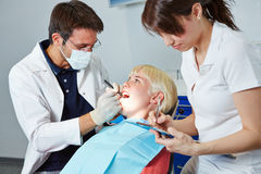 Dental assistant during apprenticeship at treatment. Dental assistant during apprenticeship taking notes at treatment of dentist stock photo
