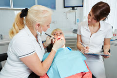 Dental assistant during apprenticeship watching dentist. At work stock photos