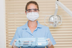 Dental assistant in blue holding tray of tools Stock Image