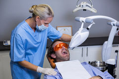 Dental assistant examining young patient mouth Royalty Free Stock Photos
