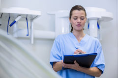 Dental assistant holding clipboard. Thoughtful dental assistant holding clipboard in dental clinic Royalty Free Stock Photos