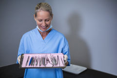 Dental assistant holding tray with equipment in dental clinic. Smiling dental assistant holding tray with equipment in dental clinic Stock Photo