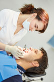 Dental assistant with male patient Stock Images