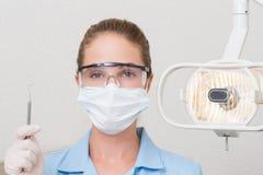 Dental assistant in mask holding dental explorer Stock Photography