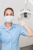 Dental assistant in mask holding light Royalty Free Stock Photography