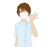 Dental assistant posing with OK sign. Winking female dental assistant with surgical mask in uniform posing with OK sign Stock Image