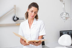 Dental assistant reading from file Royalty Free Stock Photos