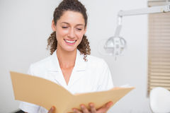 Dental assistant reading from file Royalty Free Stock Images