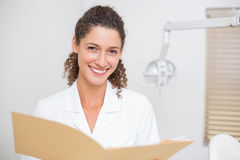 Dental assistant reading from file Stock Photos