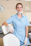 Dental assistant smiling at camera beside chair Royalty Free Stock Images
