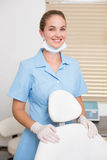 Dental assistant smiling at camera beside chair Stock Images