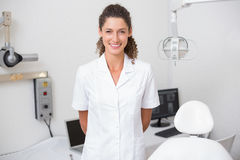 Dental assistant smiling at camera beside chair. At the dental clinic Royalty Free Stock Photos