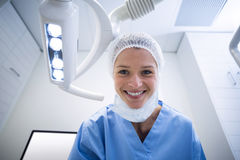 Dental assistant smiling at camera beside light. In the dental clinic Stock Photography