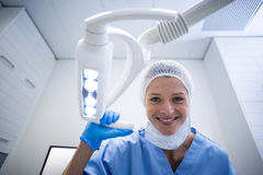 Dental assistant smiling at camera beside light. In dental clinic Royalty Free Stock Photos