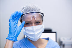 Dental assistant with surgical mask and safety glasses. Portrait of dental assistant with surgical mask and safety glasses in dental clinic royalty free stock images