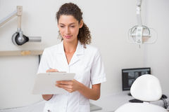 Dental assistant writing in clipboard Royalty Free Stock Photography