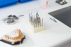 Dental burs and dental articulator in a lab. Royalty Free Stock Photos