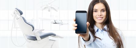 Dental care smiling woman showing smart phone on dentist clinic Royalty Free Stock Images