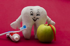Dental care. Tooth paste, apple, tooth brush and a tooth figurine on a red background Stock Photos