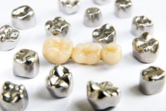 Dental ceramic, gold and metal tooth crowns on white background. Stock Photography