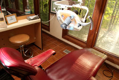 Dental chair dentist insurance. A red dental reclining chair at a dentists office royalty free stock image