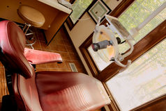 Dental chair dentist insurance. A red dental reclining chair at a dentists office royalty free stock photos