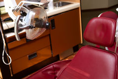 Dental chair dentist insurance. A red dental reclining chair and lamp at a dentists office stock image