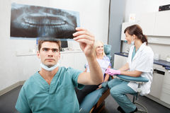 Dental Clinic. Radiodentist checking x-ray with assistant and patient having conversation in the background royalty free stock photography
