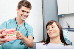 Dental Clinic Patient. Male dentist explaining a female patient denture work in dental clinic royalty free stock photos