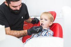 Dental clinic. Reception, examination of the patient. Teeth care. Dentist treating teeth of little boy in dentist office stock photo