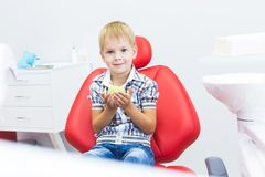 Dental clinic. Reception, examination of the patient. Teeth care. Little boy holding an apple while sitting in a dental royalty free stock photos