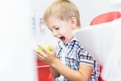 Dental clinic. Reception, examination of the patient. Teeth care. Little boy holding an apple while sitting in a dental royalty free stock photo