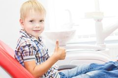 Dental clinic. Reception, examination of the patient. Teeth care. Little boy showing thumb up sign at dentist`s office stock image