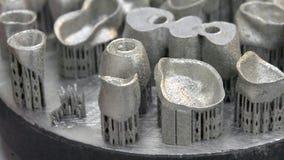 Dental crowns printed on metal 3d printer laser sintering machine. Object printed on metal 3d printer. Dental crowns created in a laser sintering machine close stock video footage