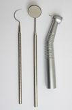 Dental drill, mirror and probe. Dental instruments. Mirror, probe and handpiece (drill) with bur Stock Photo