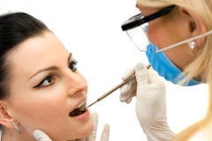 Dental examination. The doctor examining the patient with dental mirror Stock Photos