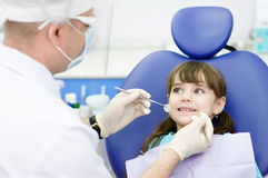 Dental examining being given to  girl by dentist. Dental examining being given to little girl by dentist Royalty Free Stock Image