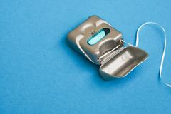 Dental floss on a blue background with copy space stock image
