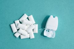 Dental floss in white container and heap of chewing gums on blue background, top view.  stock photos