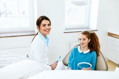Dental Health. Dentist And Happy Girl In Dentistry Office. Dental Health. Female Dentist And Little Happy Girl Sitting In Dentistry Office. High Resolution stock image