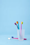 Dental hygiene. Four toothbrushes and speculum (dental mirror) - dental hygiene. Selective focused on front toothbrush, blue background Royalty Free Stock Image