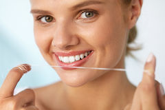Dental Hygiene. Beautiful Woman Flossing Healthy White Teeth Stock Photo