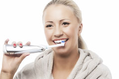 Dental Hygiene Concept:Caucasian Woman Brushing Her Teeth With M. Odern Electric Toothbrush. Against Pure White Background. Horizontal Image stock images