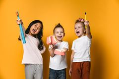 Dental hygiene. happy little cute children with toothbrushes. Three children hold toothbrushes, girls show their toothbrushes and the boy holds a model of the royalty free stock images