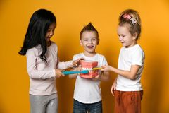 Dental hygiene. happy little cute children with toothbrushes. Three children with toothbrushes and a kissuos mock-up with zooms stand over yellow background stock images