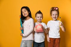 Dental hygiene. happy little cute children with toothbrushes. Three childrens with toothbrushes and a kissuos mock-up with zooms stand over yellow background stock photography