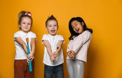 Dental hygiene. happy little cute children with toothbrushes. Three joyful friends of children hold toothbrushes. The concept of health, oral hygiene, people royalty free stock photo
